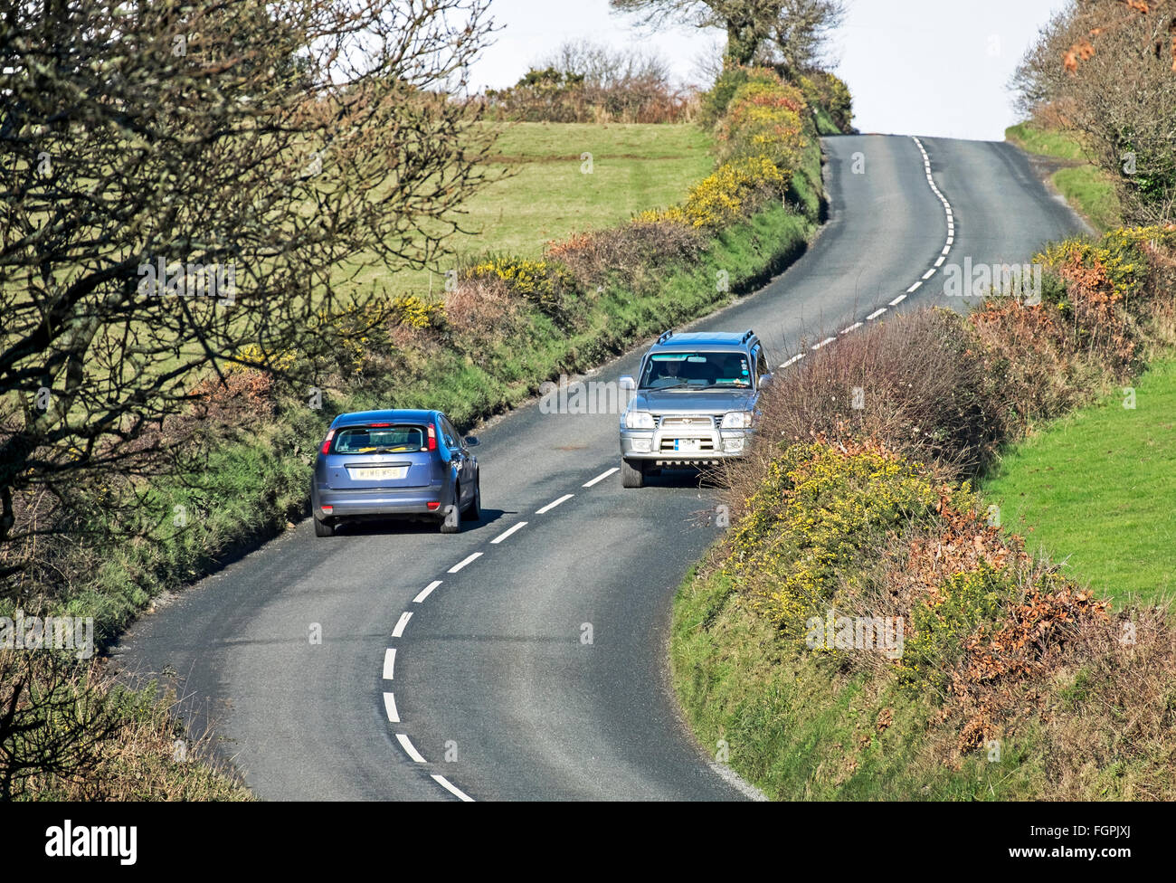 Two vehicles passing on a bend on a country road in cornwall, uk - Stock Image