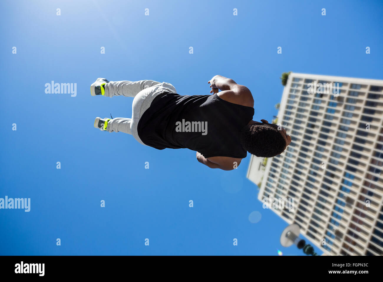 Athletic man doing back flip in the city - Stock Image
