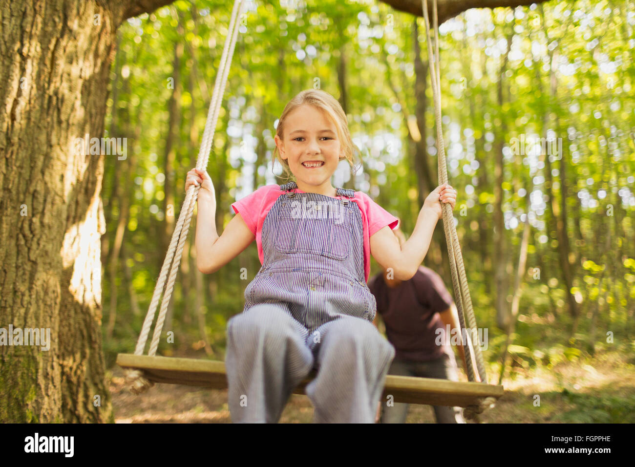 Portrait smiling girl swinging on rope swing in forest - Stock Image
