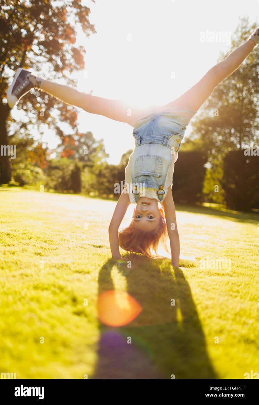Girl doing handstand in sunny garden - Stock Image