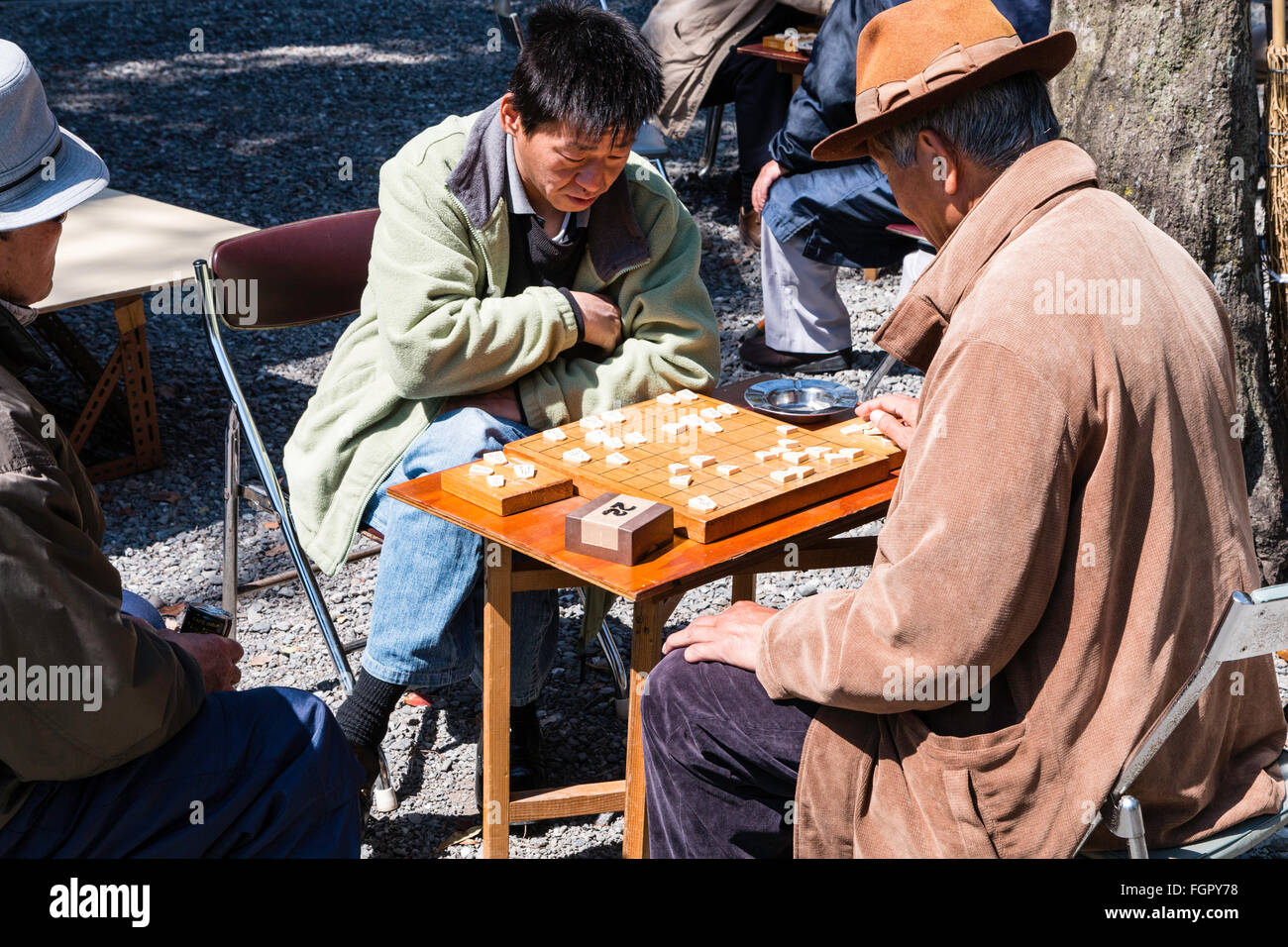 Japan, Kochi. Homeless unemployed men, all wearing coats, sitting at tables in the park playing shogi games in the - Stock Image
