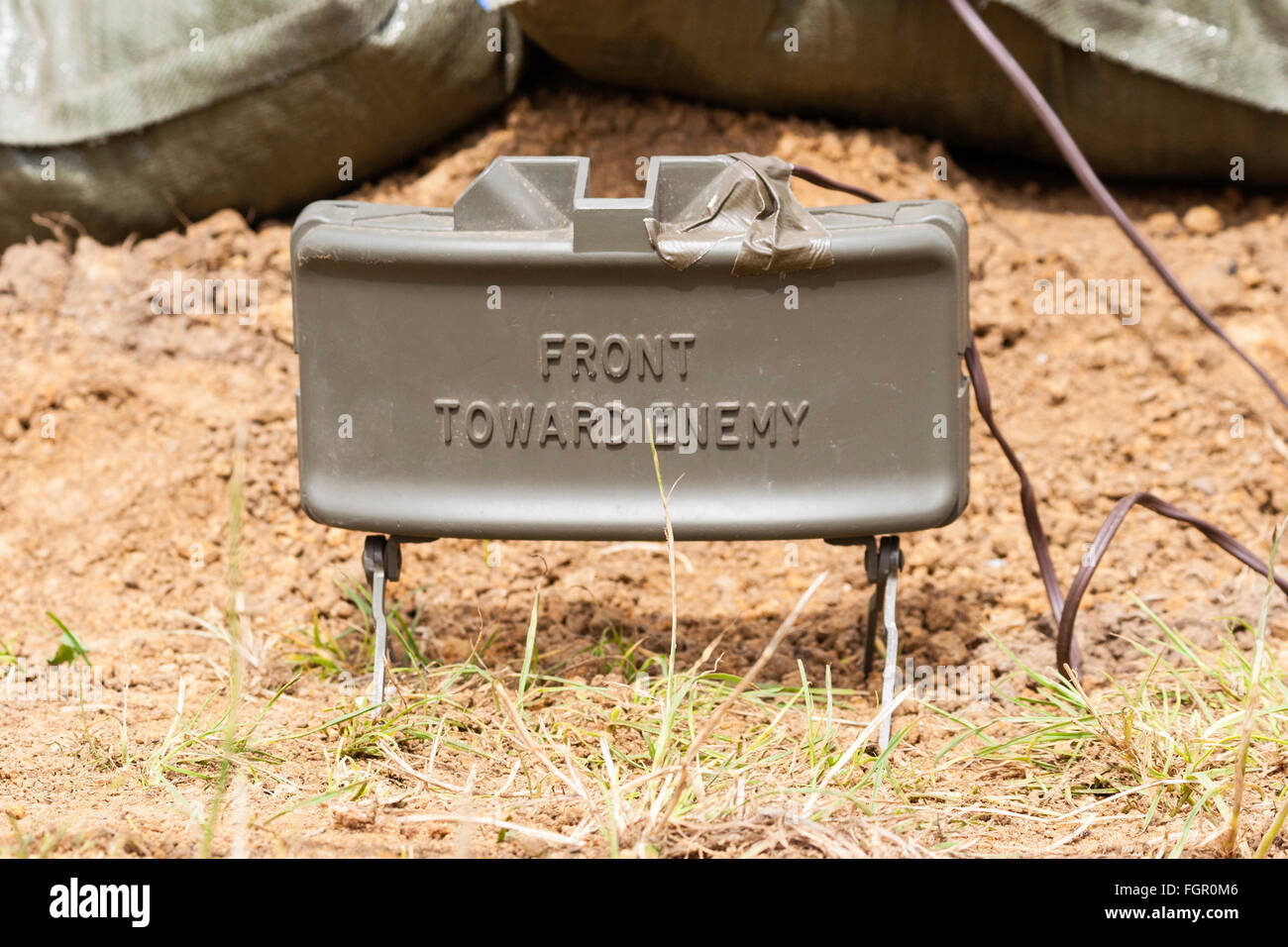Vietnam war re-enactment. M18 Claymore mine with M4 blasting cap set up as booby trap just above the ground. On - Stock Image