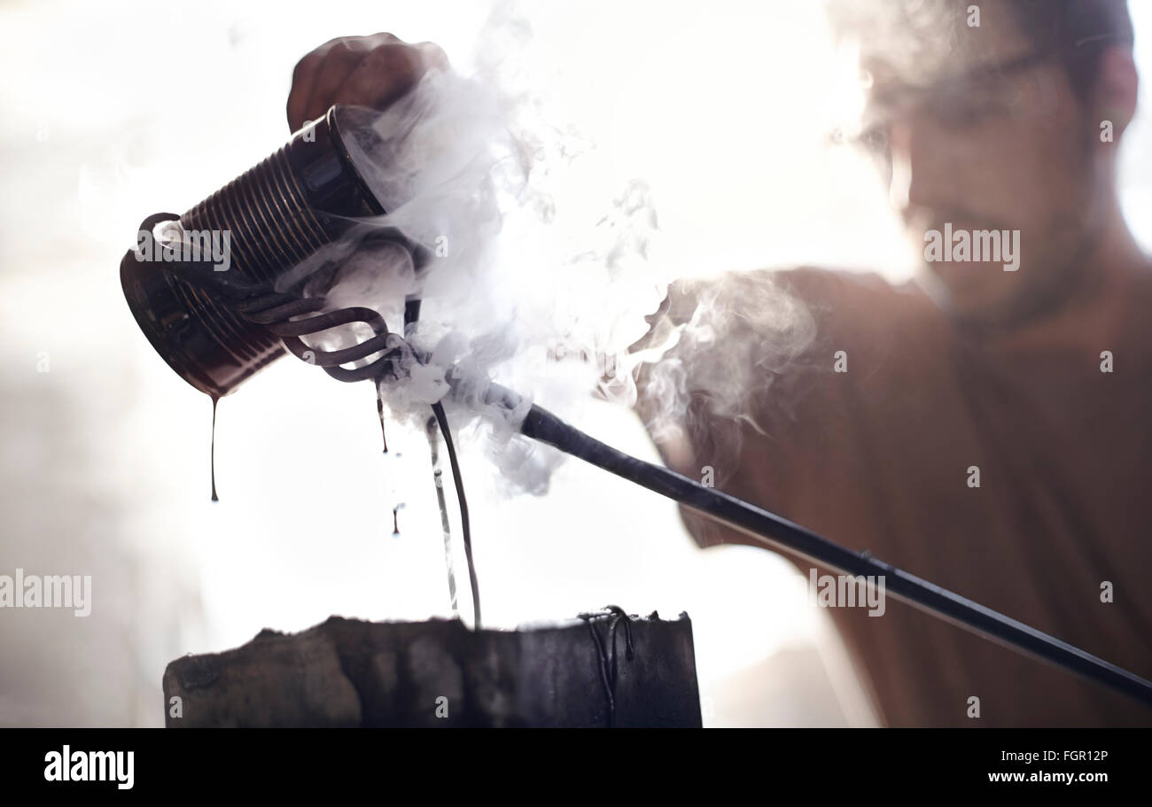 Blacksmith pouring steaming liquid over wrought iron - Stock Image