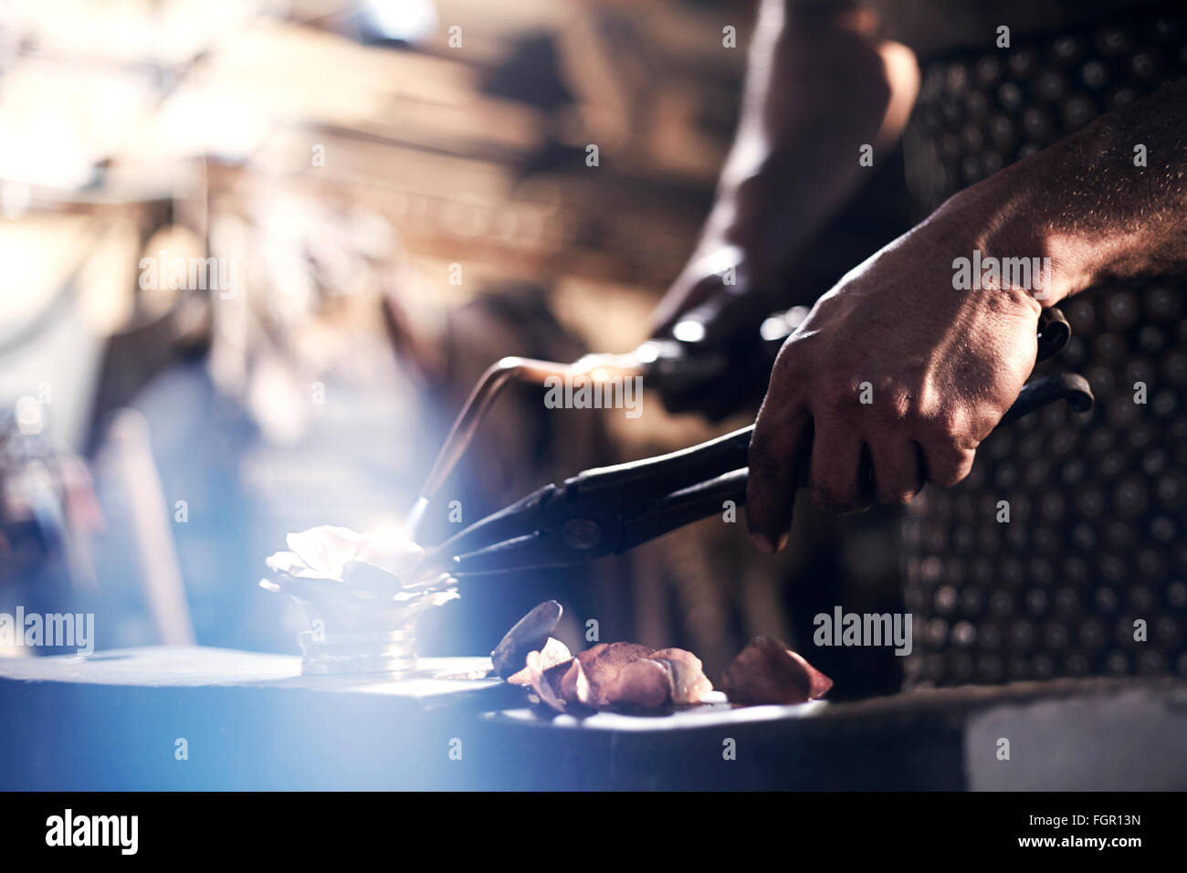 Close up of blacksmith heating metal with blowtorch in forge - Stock Image