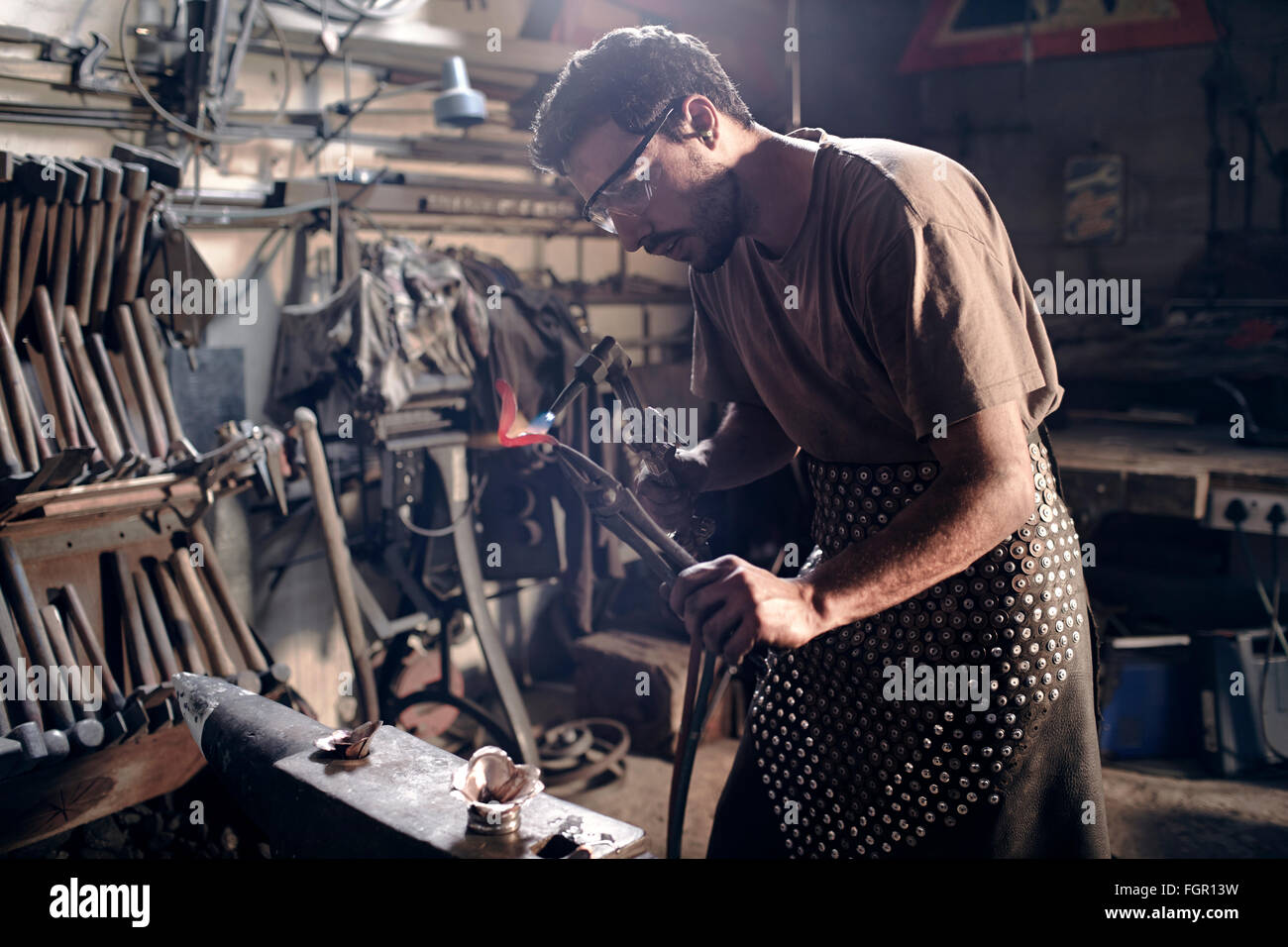 Blacksmith heating metal with blowtorch in forge - Stock Image