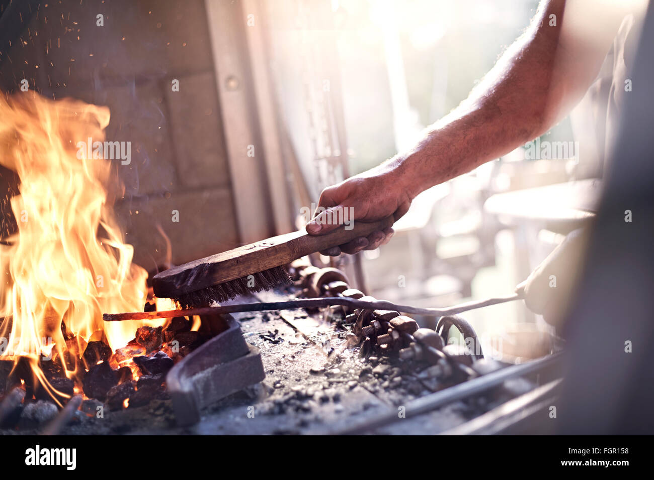 Blacksmith heating tool at fire in forge - Stock Image