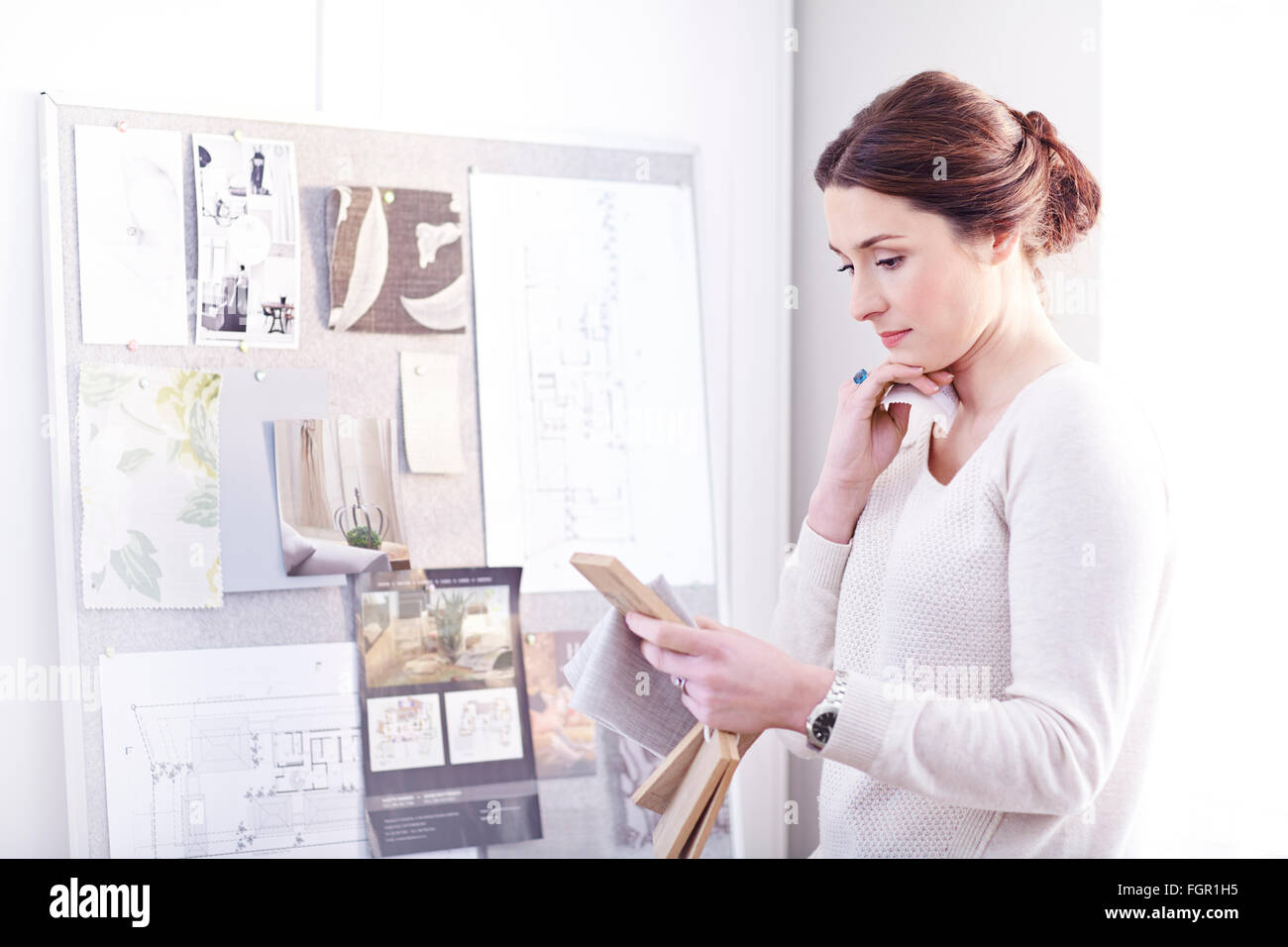 Interior designer viewing swatches in office - Stock Image