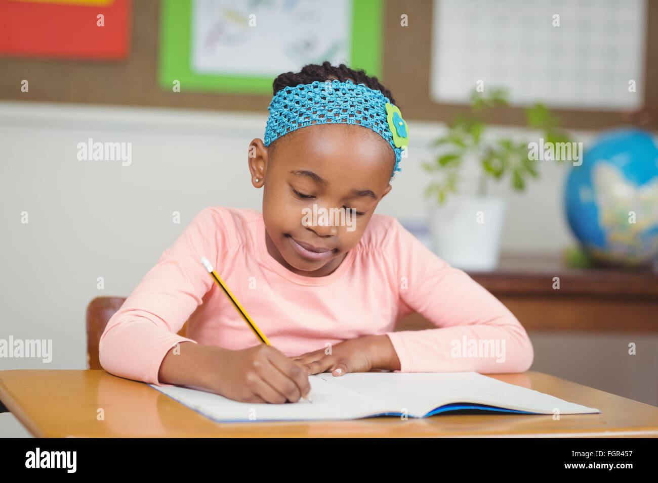 Focused pupil working at her desk in a classroom - Stock Image