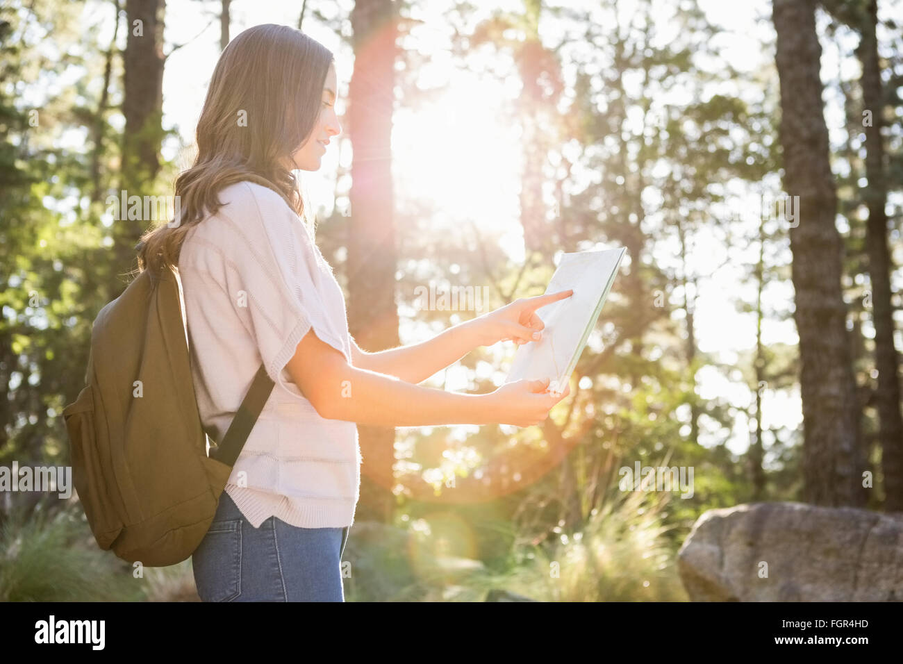 Pretty brunette hiker reading map - Stock Image