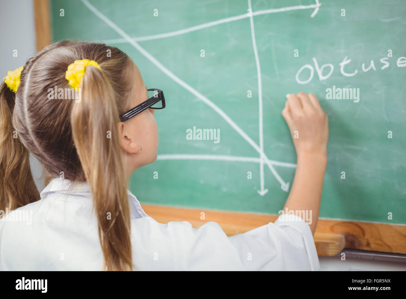 Pupil with lab coat writing on chalkboard in a classroom - Stock Image