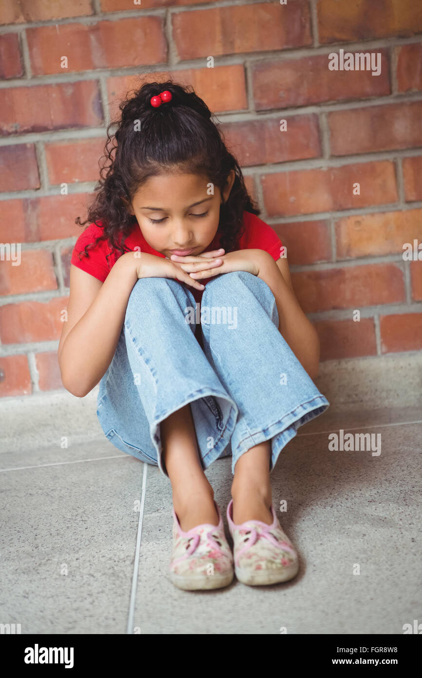 Upset lonely girl sitting by herself - Stock Image