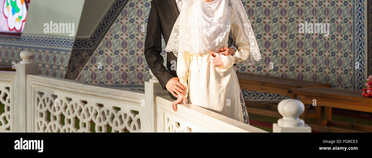 Just married muslim couple posing in front of mosque - Stock Image