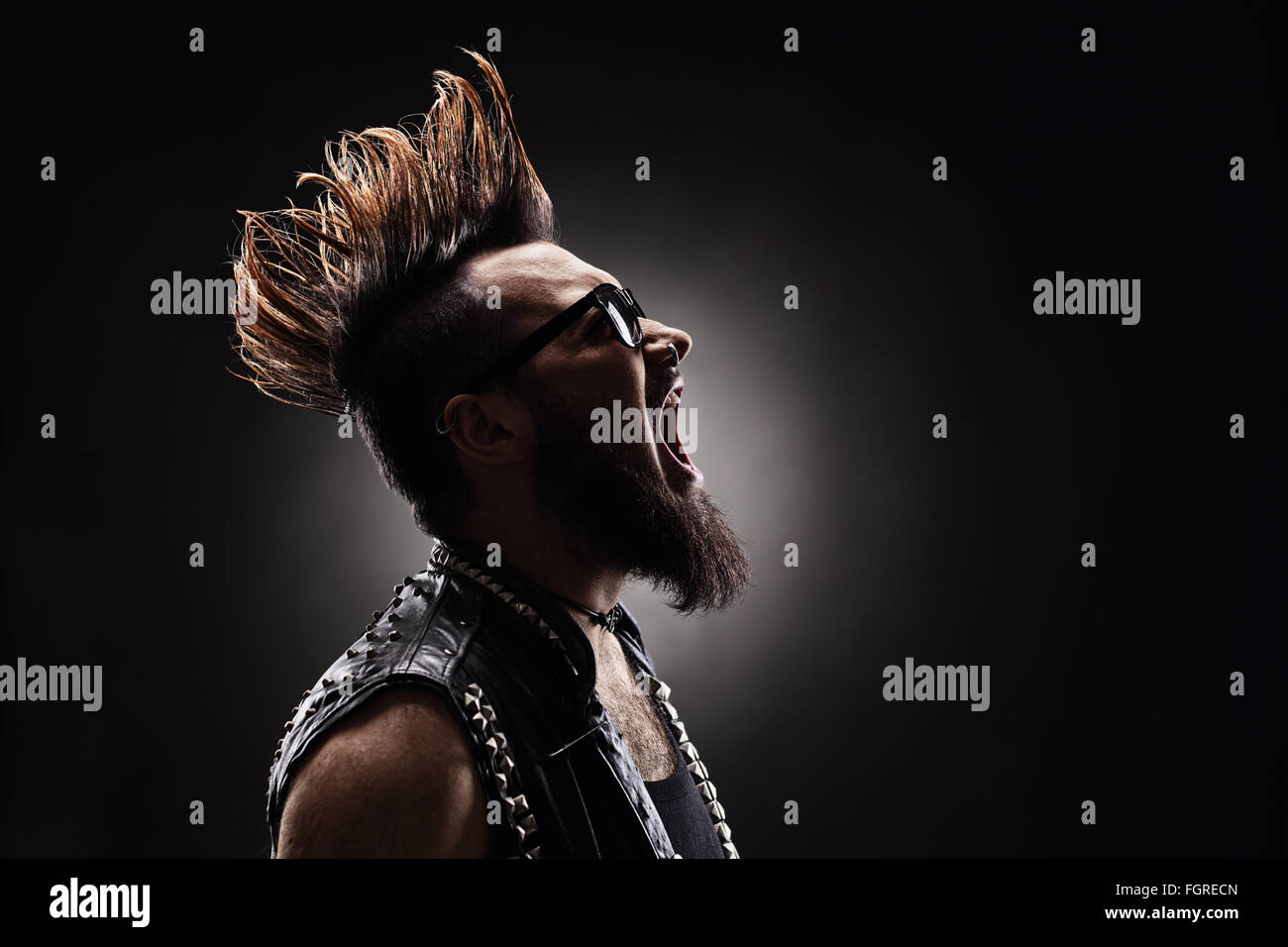 Profile shot of an angry punk rocker shouting on dark background - Stock Image