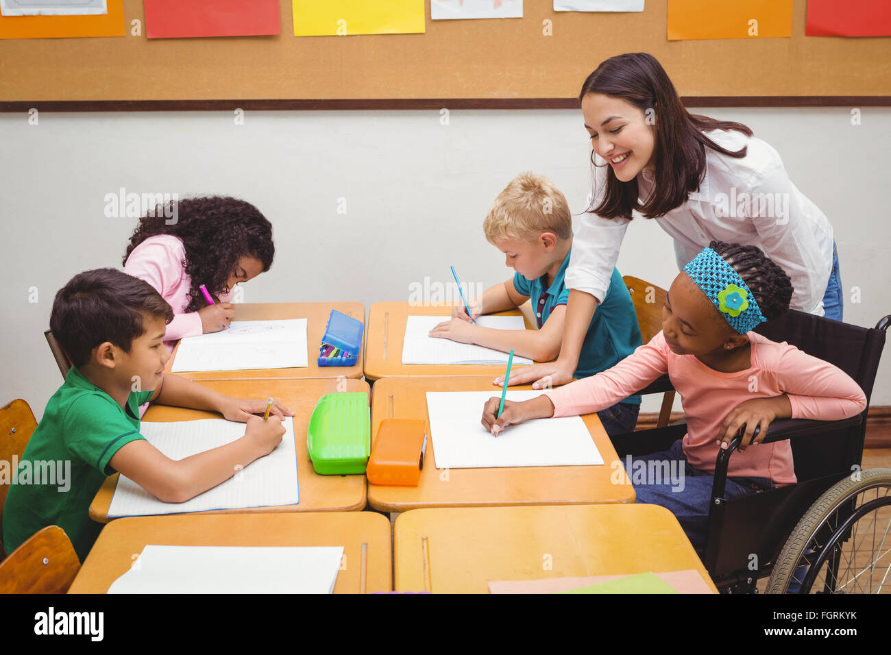 Happy teacher helping her students - Stock Image