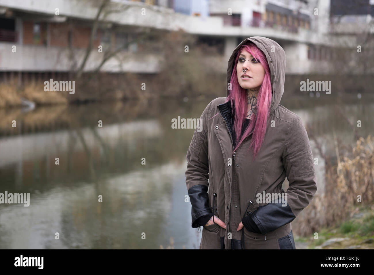 woman with pink hair in bleak surroundings - Stock Image
