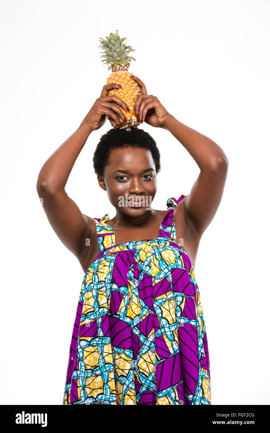 Pretty happy african american young woman in bright sundress holding pineapple on her head over white background - Stock Image