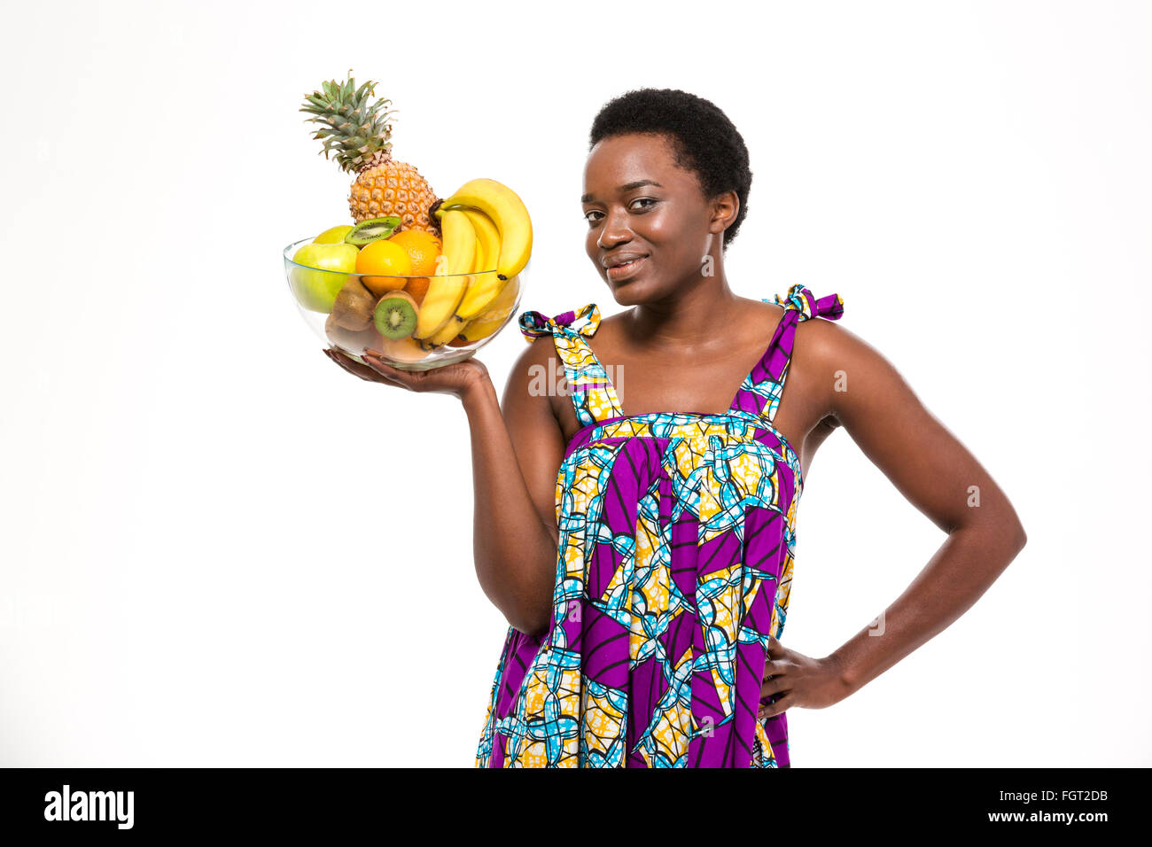 Cheerful attractive african american young woman in bright sundress standing and holding glass bowl with fruits - Stock Image
