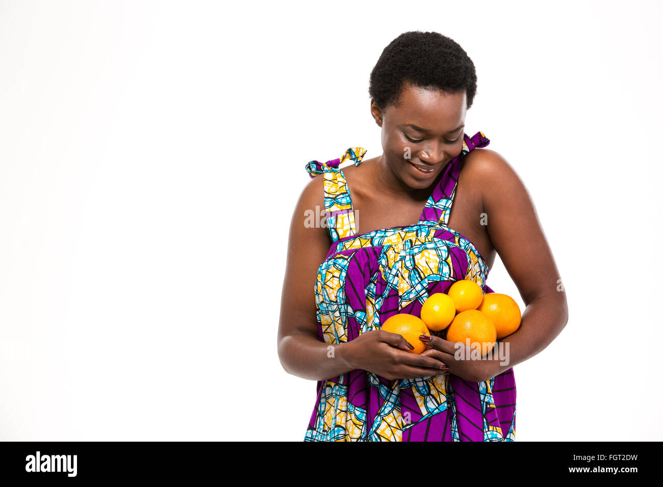 Pretty happy african american young woman in bright sundress with oranges and lemons over white background - Stock Image