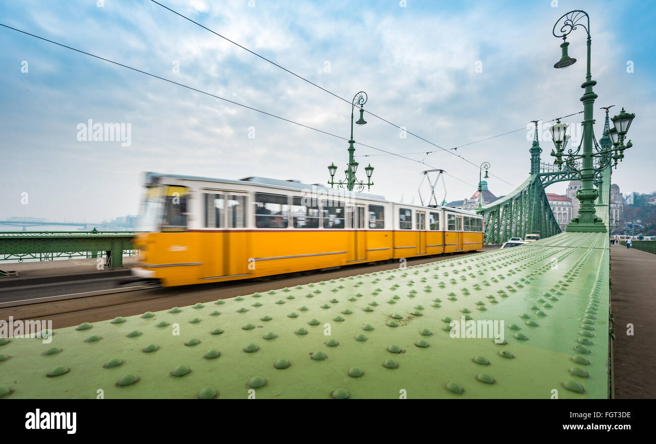 Wide view on yellow Tram crossing Liberty bridge in Budapest, Hungary, Europe. Major landmark and tourist attraction. Stock Photo