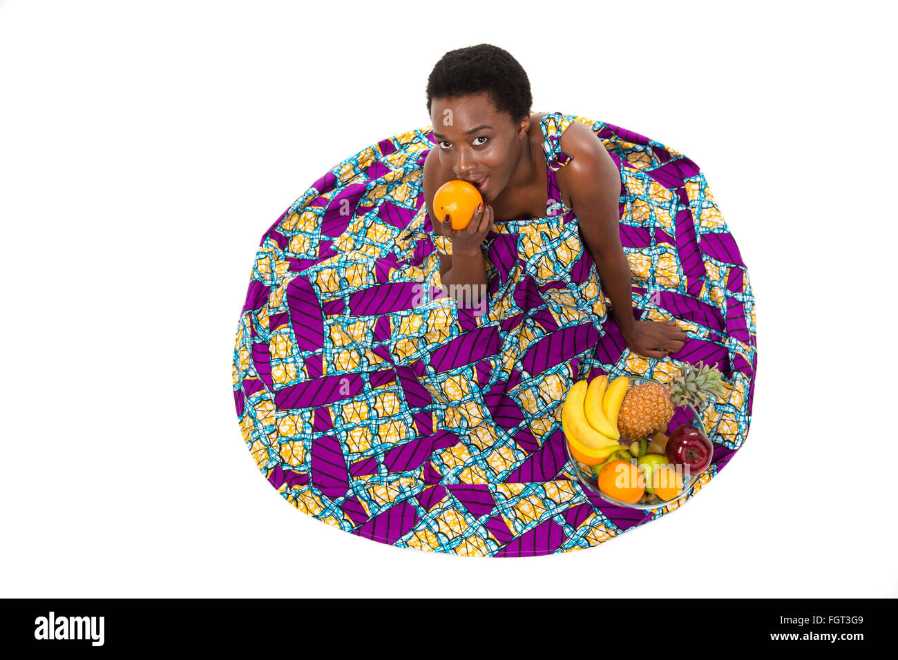 Top view of happy lovely african american young woman in colorful sundress sitting and eating orange over white - Stock Image
