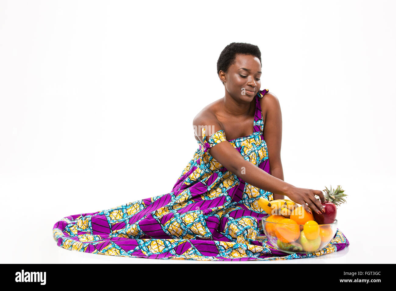Smiling charming african american young woman in bright sundress sitting with glass bowl of fruits over white background - Stock Image