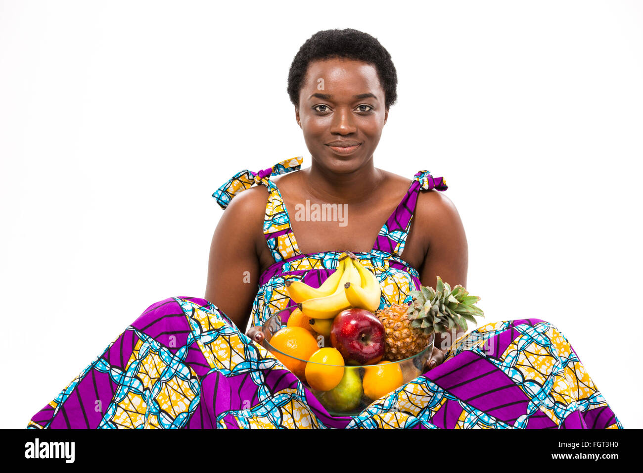 Cheerful beautiful african american young woman in bright sundress sitting and holding different exotic fruits over - Stock Image