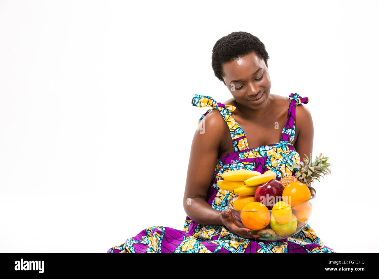 Pretty happy african american young woman in bright sundress sitting and looking at fresh exotic fruits over white - Stock Image