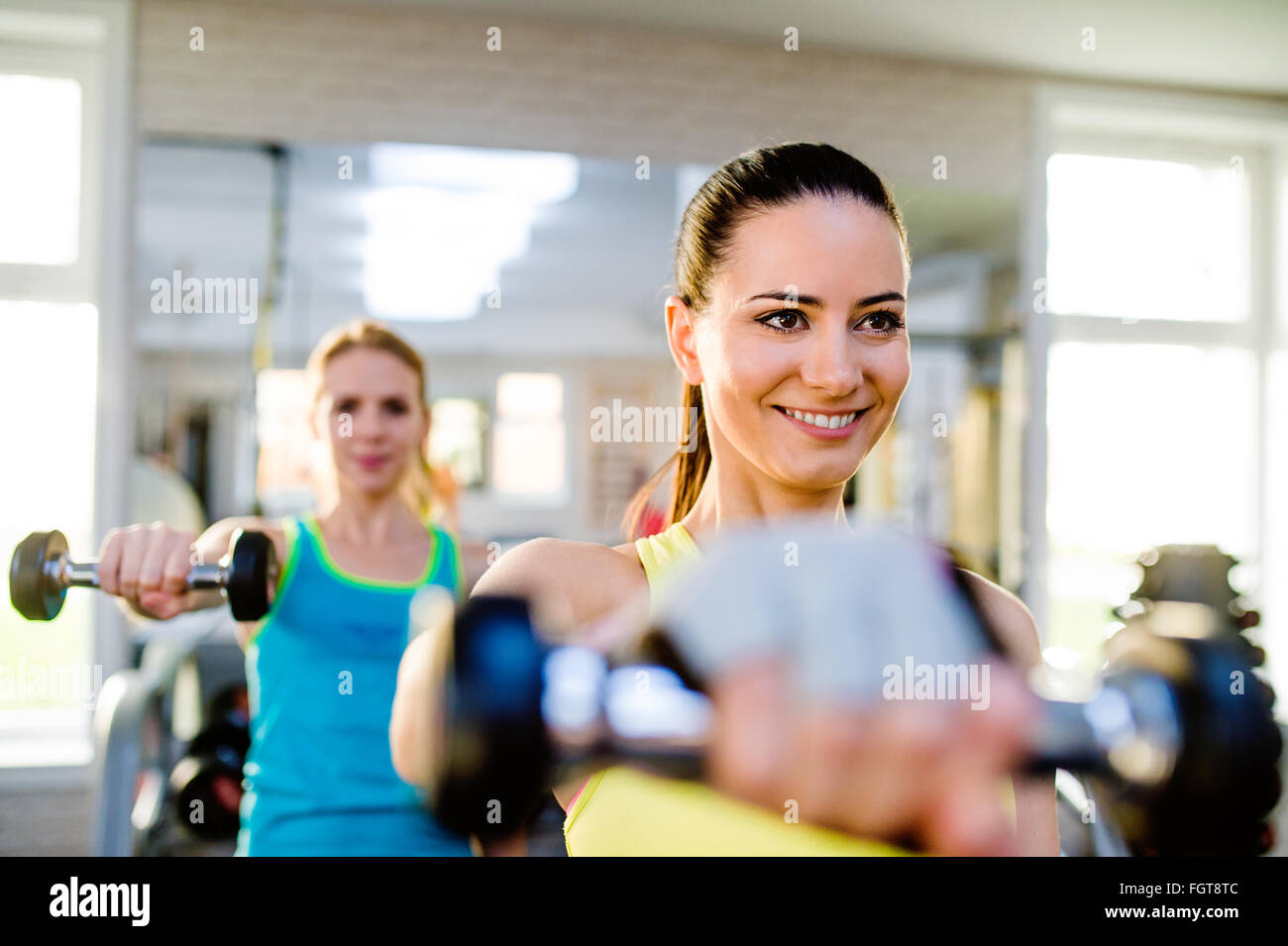 Two fit women in gym working out with weights - Stock Image