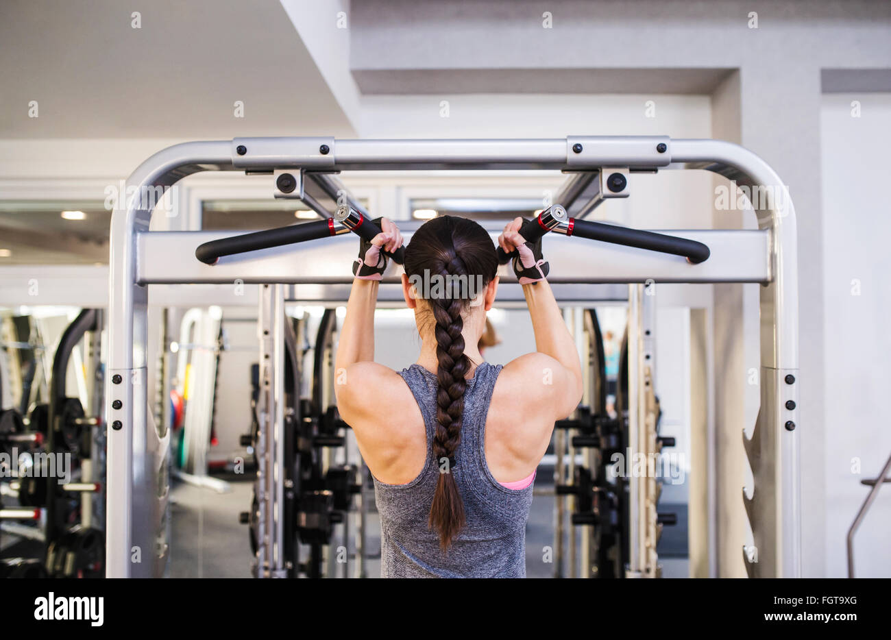 Woman in gym flexing back muscles on cable machine - Stock Image
