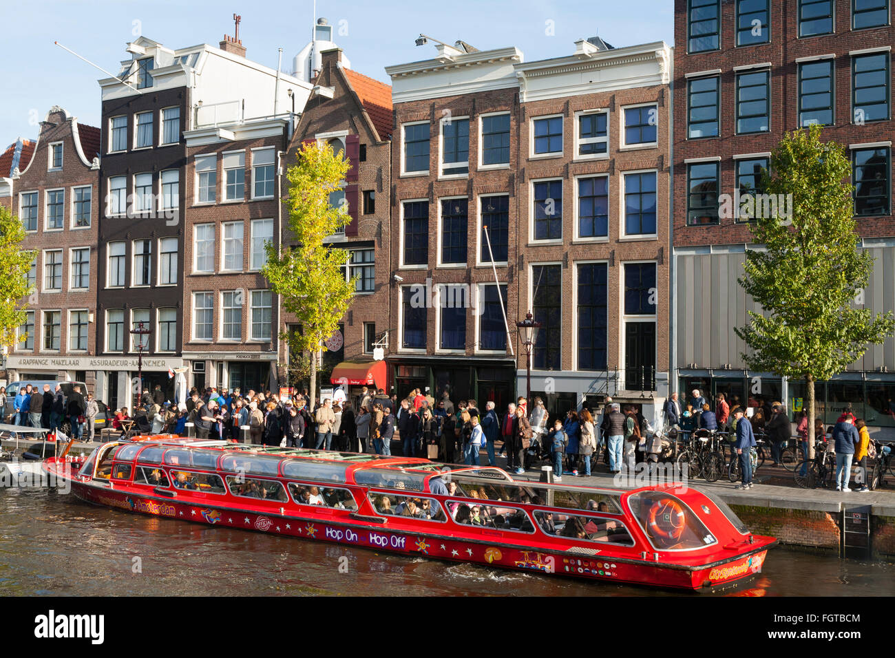 Tourist sight seeing boat with tourists / visitors in front of Anne Frank 's House / museum in Amsterdam Holland - Stock Image