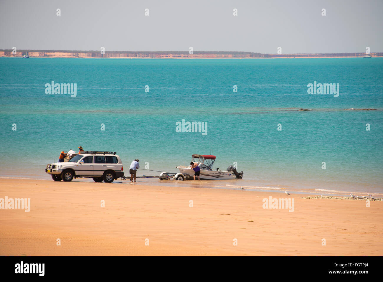Launching a boat on a beach facing Roebuck Bay. It  is close to the Port of Broome in Broome, a coastal, pearling - Stock Image