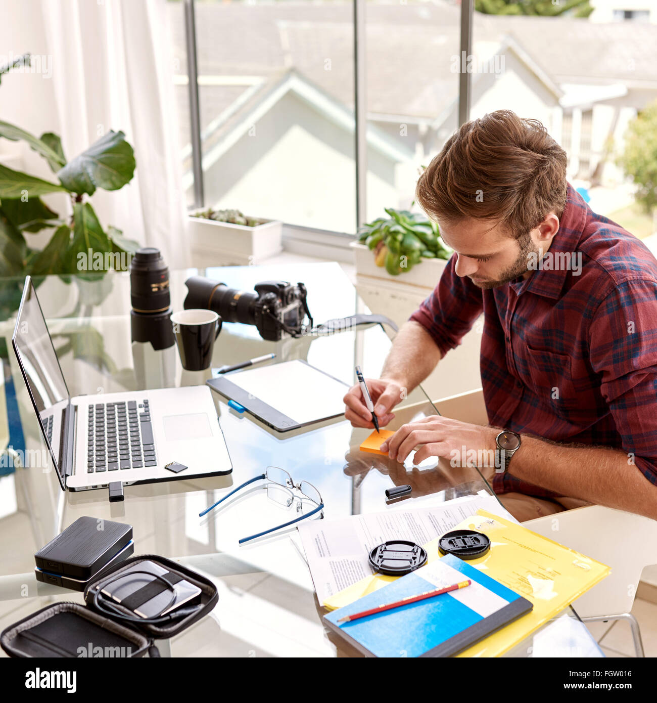 Square crop image of an entrepreneur busy working - Stock Image