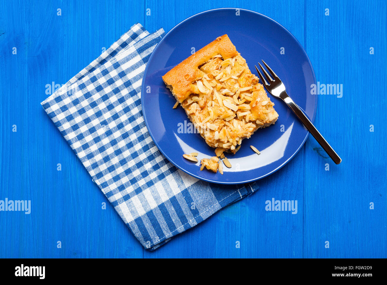 Piece of apple cake with almond slivers on blue plate and checkered napkin on wooden blue table, top view - Stock Image