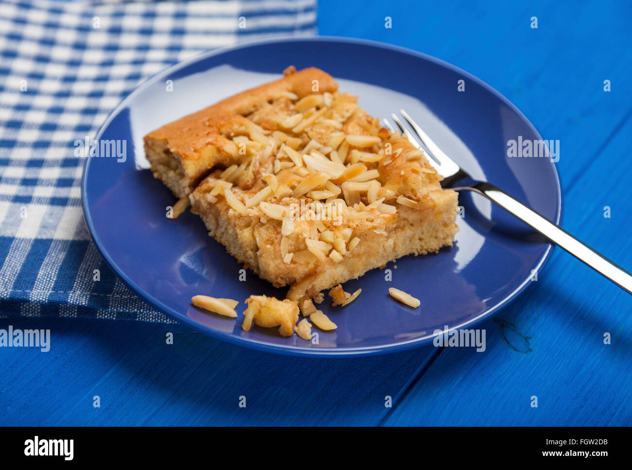 Piece of apple cake with almond slivers on blue plate and checkered napkin on wooden blue table - Stock Image