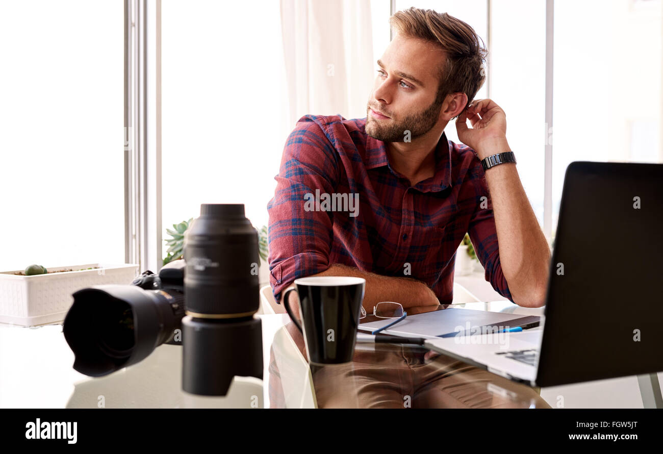 Entrepreneurial photographer looking off camera at his desk - Stock Image