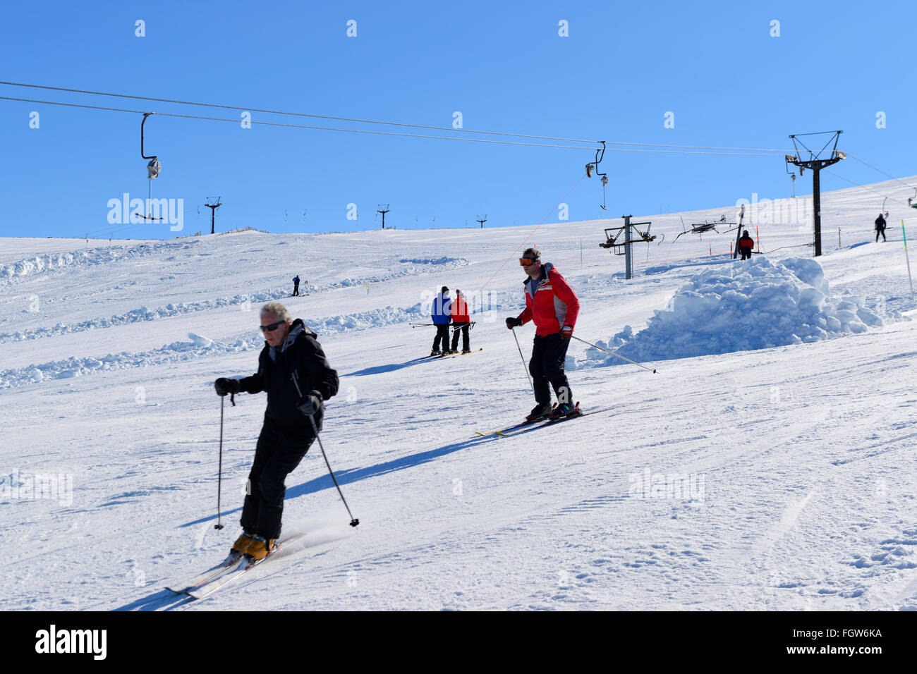 Skiers on downhill run at Cairngorm Mountain Ski Centre, Aviemore, Scottish Highlands, UK - Stock Image