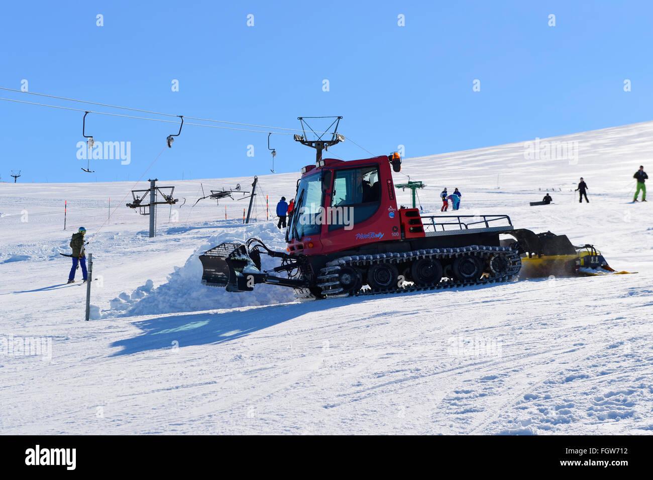 Piste basher grooming ski run at Cairngorm Mountain Ski Centre, Aviemore, Scottish Highlands, UK - Stock Image