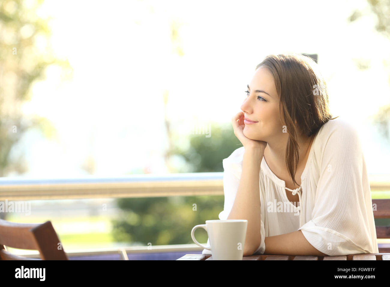Pensive happy woman remembering looking at side sitting in a bar or home terrace - Stock Image