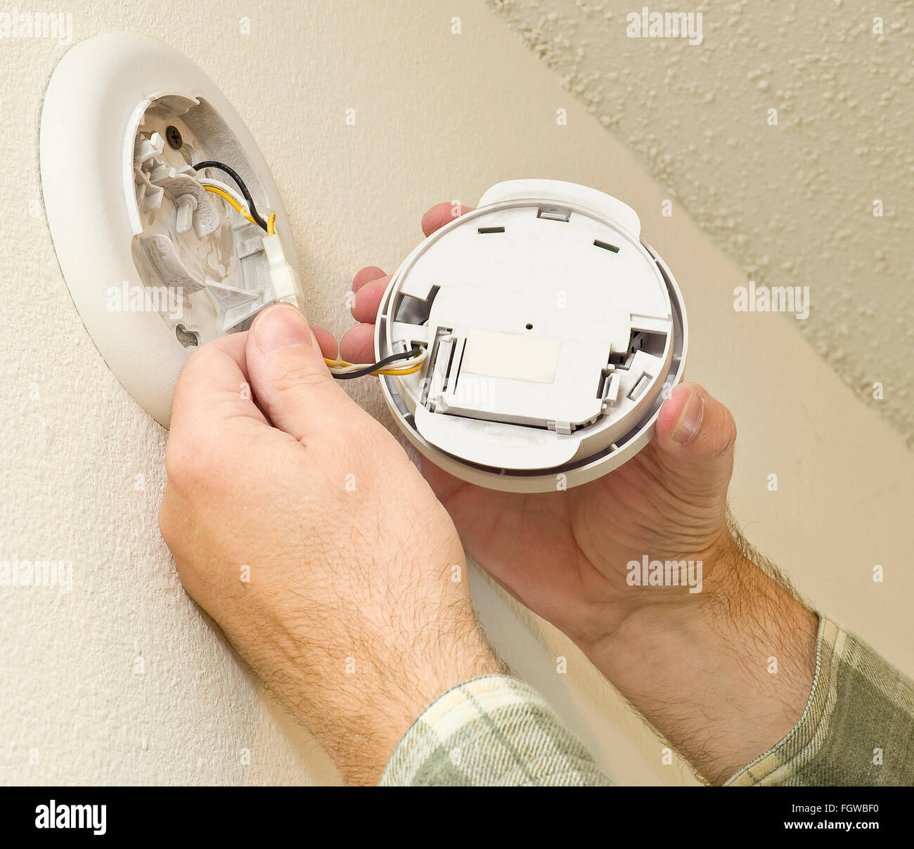 Removing Smoke Detector to Change the Battery - Stock Image