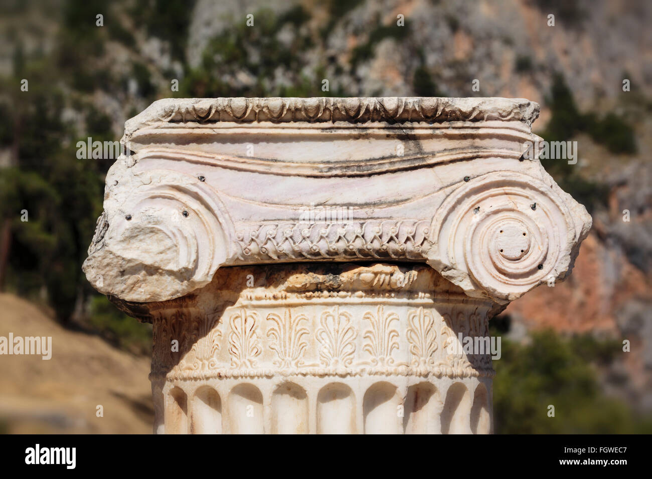 Ancient Delphi, Phocis, Greece.  Broken column on the Sacred Way crowned by Corinthian capital - Stock Image