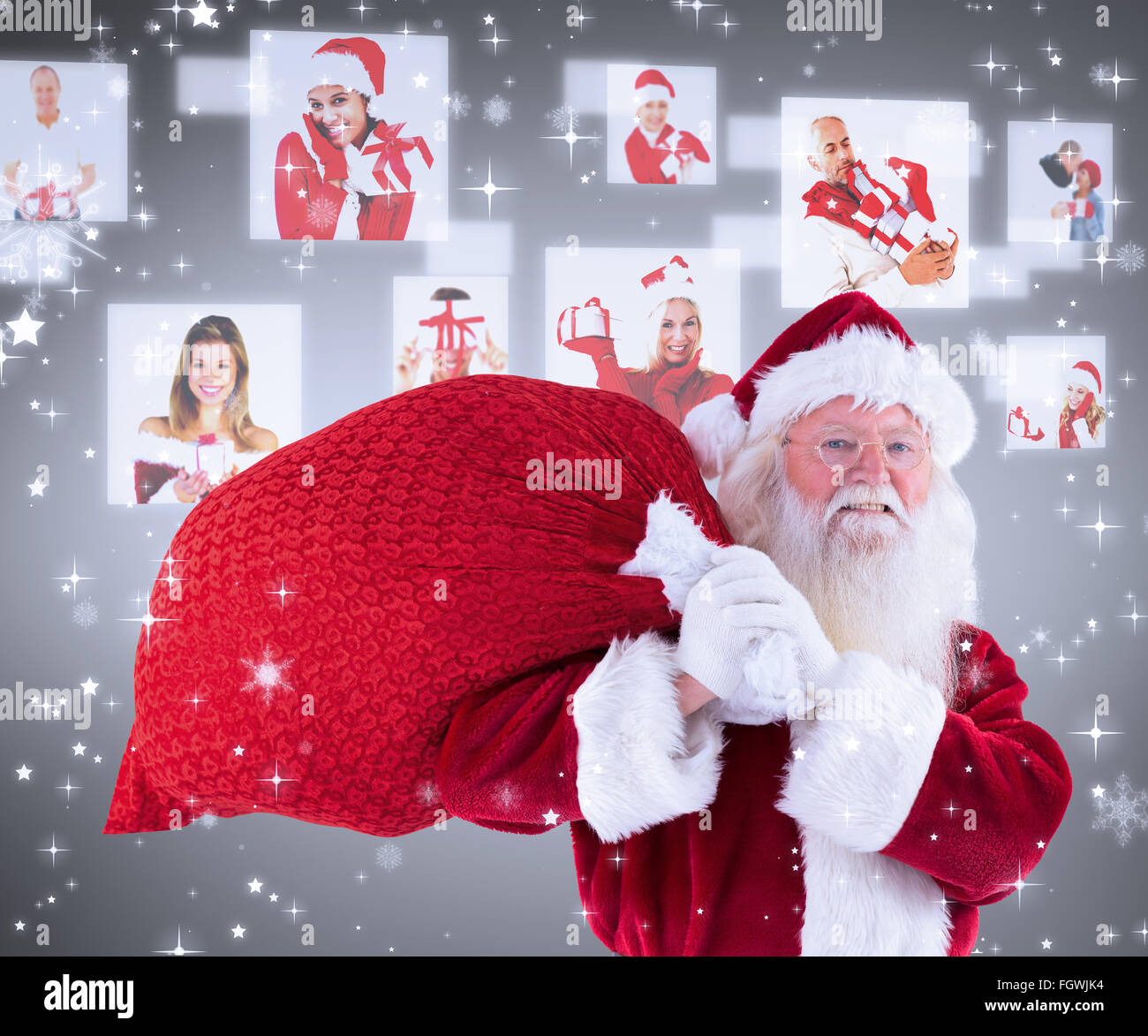 Composite image of santa carries his red bag and smiles - Stock Image