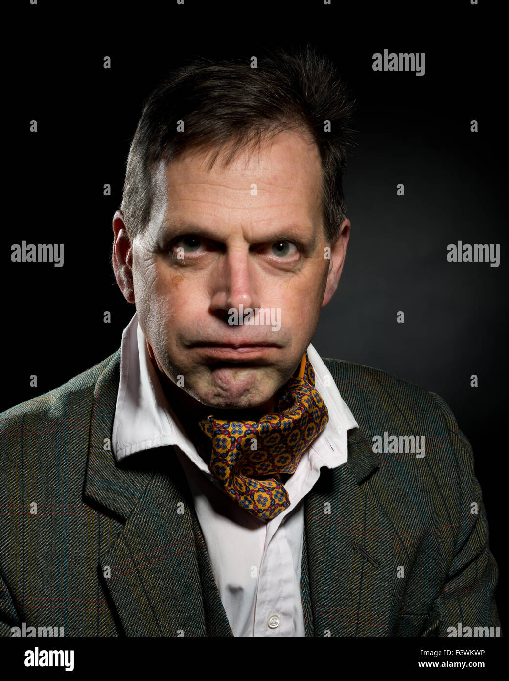 Middle aged slightly grumpy man. Dressed in tweed suit with cravat. Slightly annoyed or unamused. - Stock Image