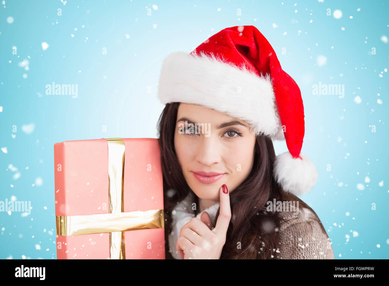Composite image of festive brunette holding gift - Stock Image