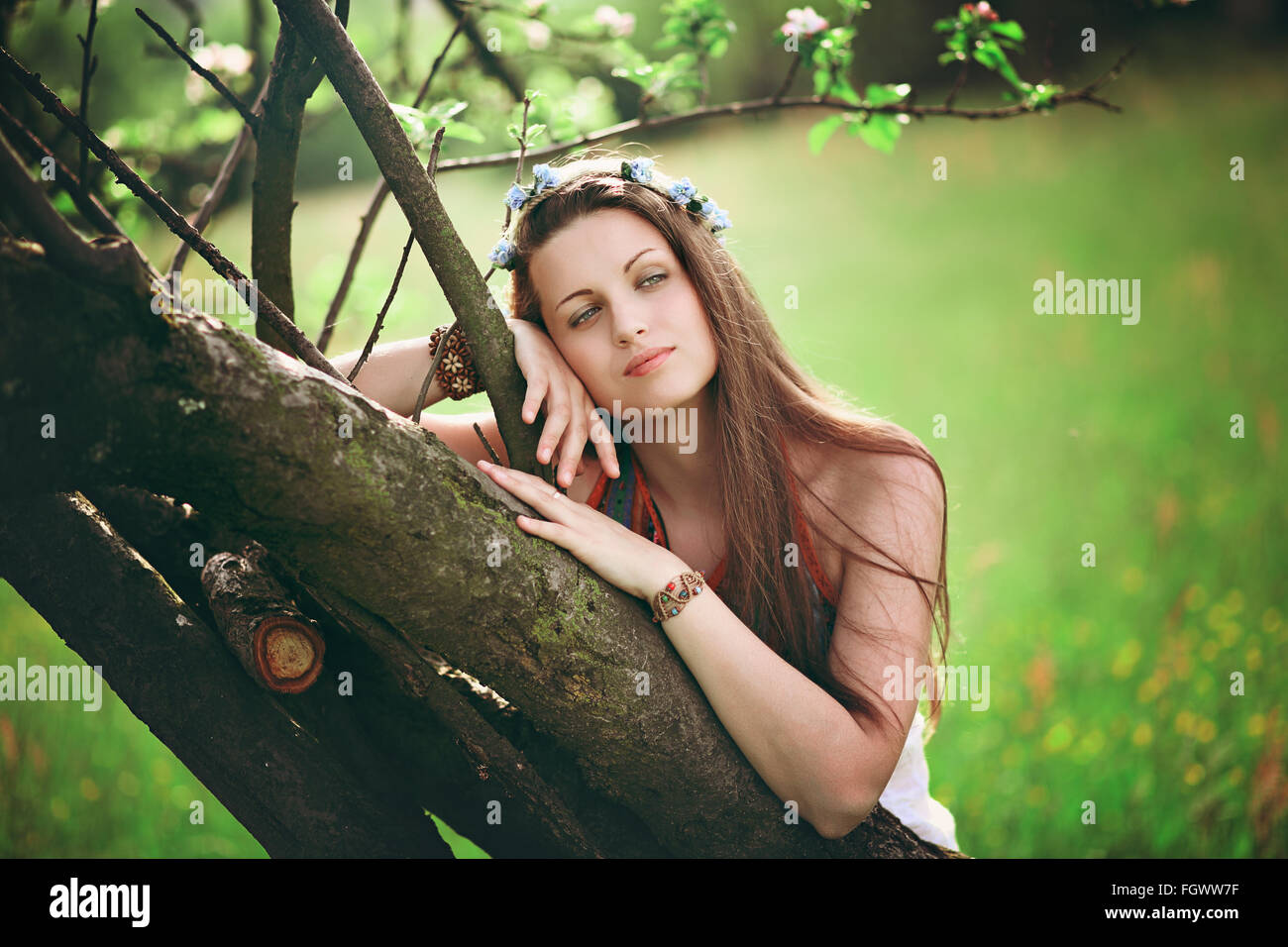 Bohemian woman leaning on spring tree. Hippie and romantic - Stock Image