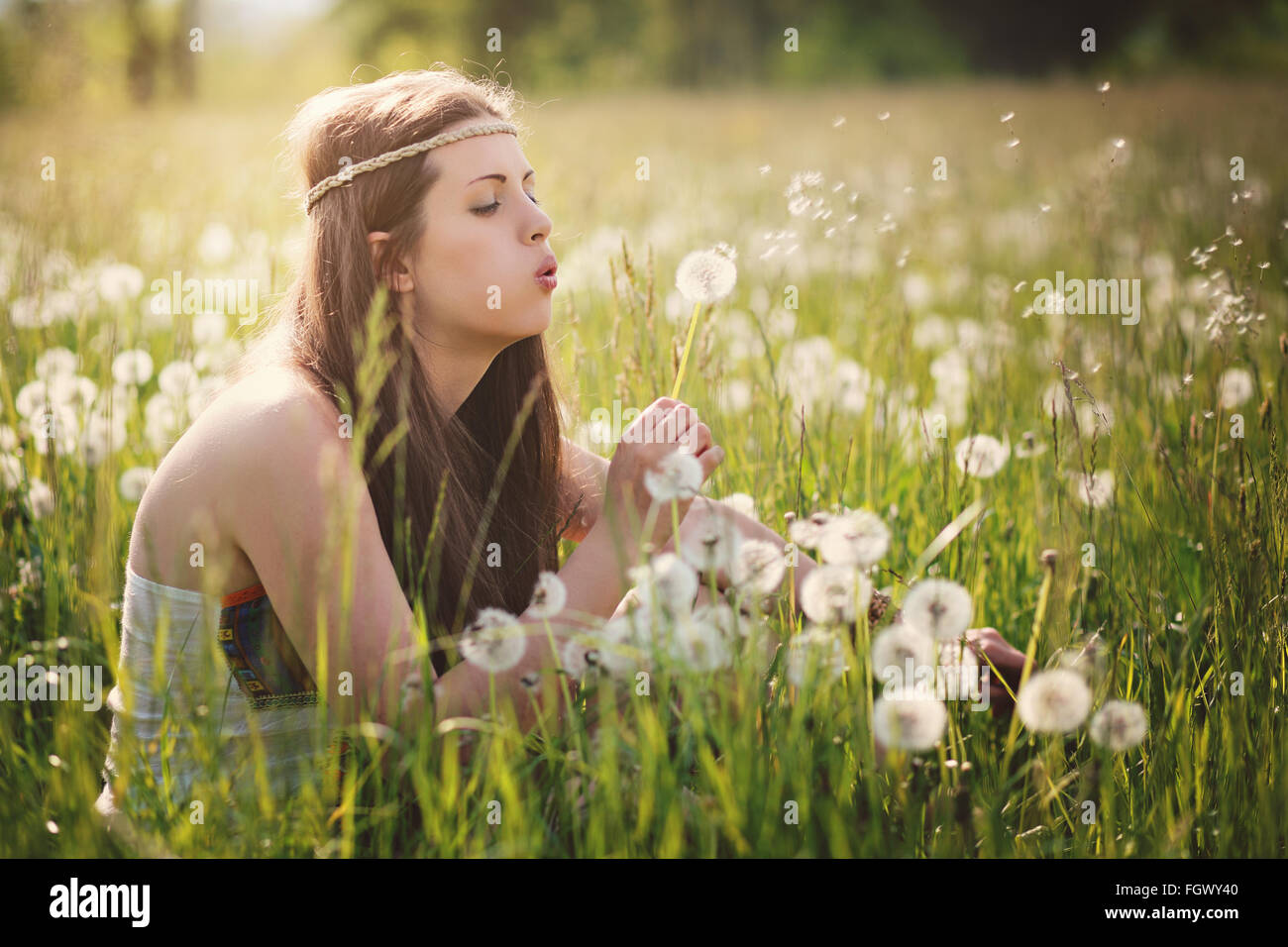 Beautiful hippie woman blowing dandelion flowers. Nature harmony - Stock Image