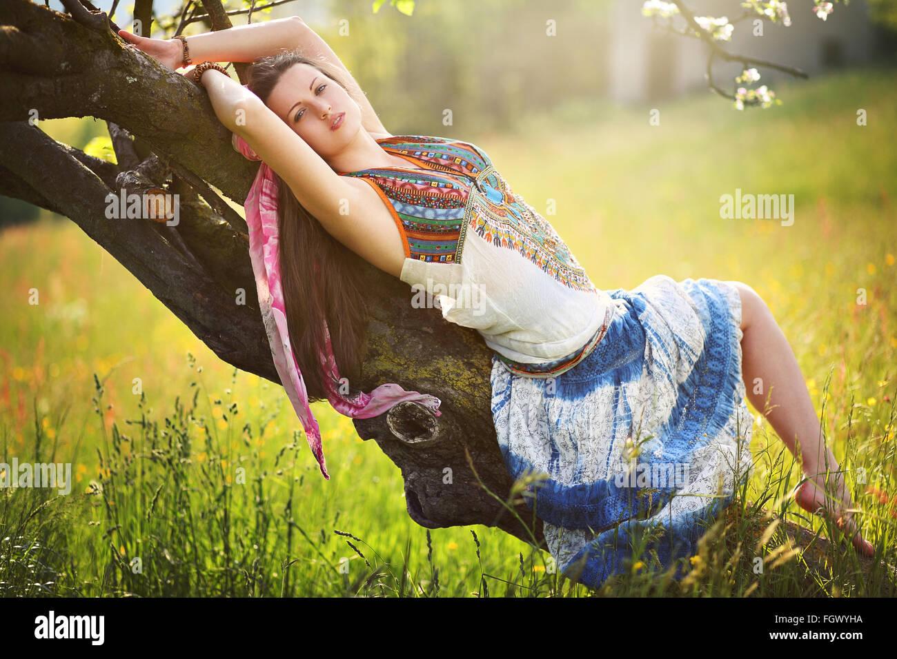 Beautiful romantic hippie posing in spring meadow. Gypsy dress - Stock Image