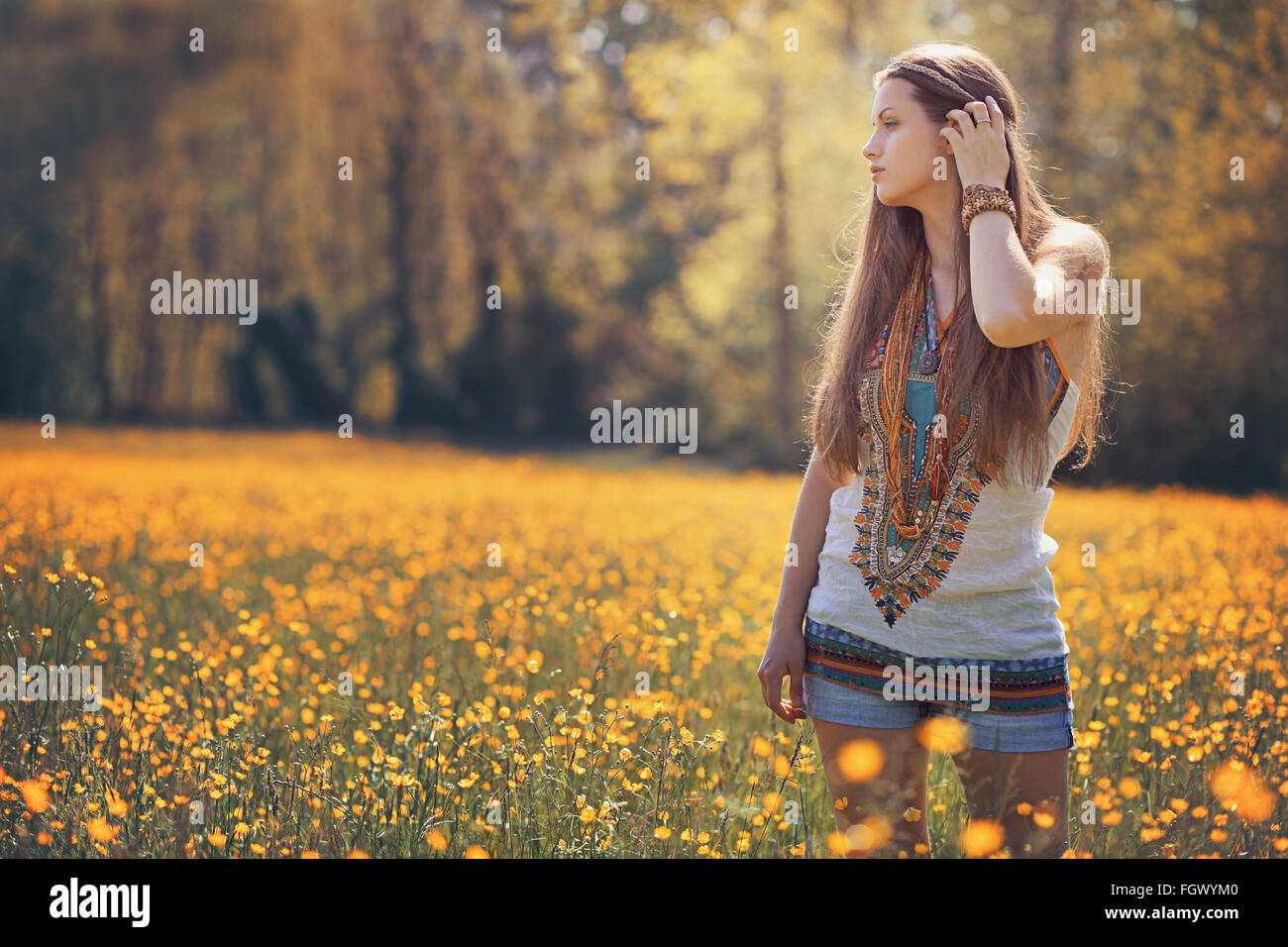 Beautiful hippie woman in flower field . Summer colors - Stock Image