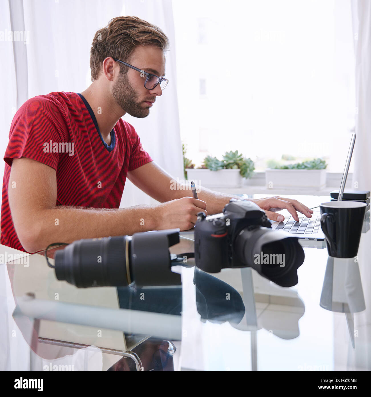 Young caucasian image enthusiast hard at work - Stock Image