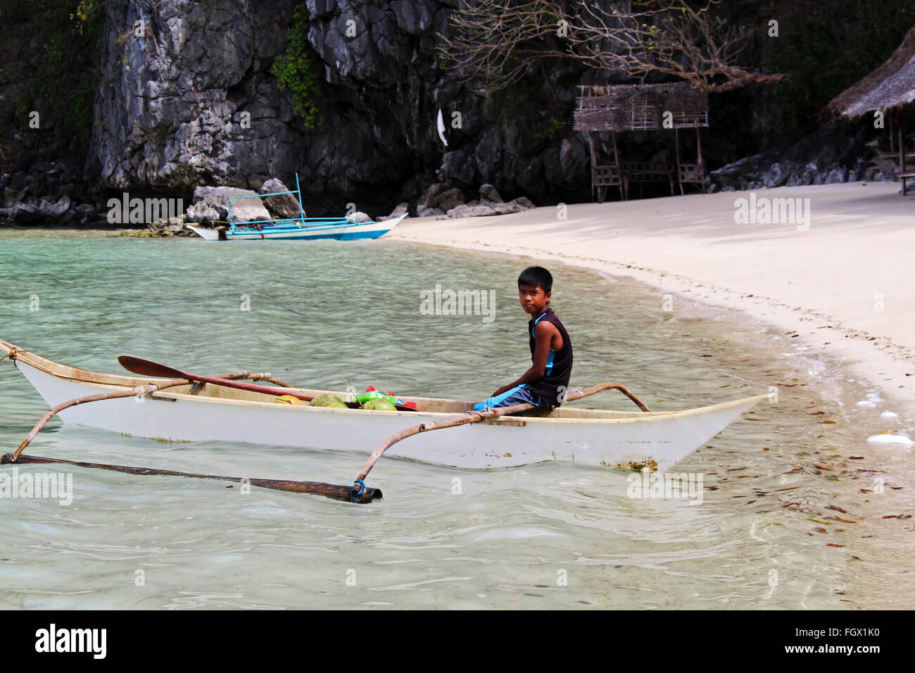 PALAWAN/PHILIPPINES - CIRCA DECEMBER 2015: Local boy on a typical filipino boat called balangay on one of the islands - Stock Image