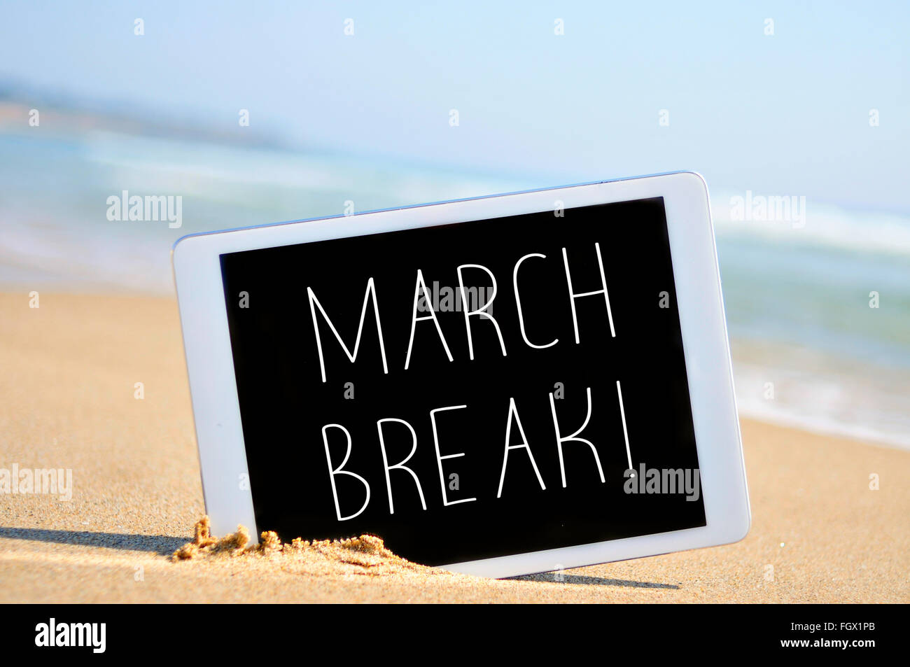 a tablet computer with the text march break written in it on the sand of a beach - Stock Image